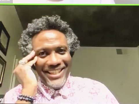 A smiling Black man with salt-and-pepper hair and pink shirt.
