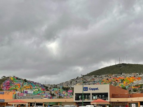 Hills with brightly colored buildings and gray clouds overhead