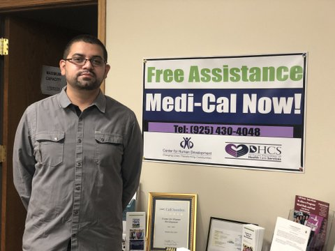 """Latino man with close cut hair and beard, glasses and gray button-down shirt next to a table with pamphlets and other written material and a sign that says """"Free assistance Medi-Cal now!"""""""