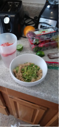 A bowl of mac and cheese with broccoli on a kitchen counter