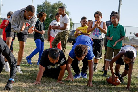 A Black man mid-applause and a group of children stand around three boys crouched on all fours in a field.