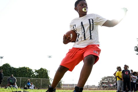"""A young Black boy wearing a white T-shirt with """"GAP"""" in big letters and orange shorts with a football under one arm and the other outstretched"""