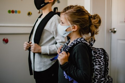 Side view of two kids wearing masks and backpacks