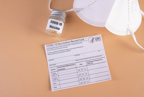 A blank COVID-19 vaccination record card, white mask and small jar that says COVID-19 vaccine