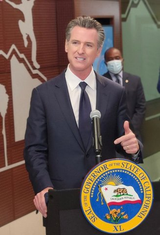 Gavin Newsom at a lectern with a man in a medical mask behind him