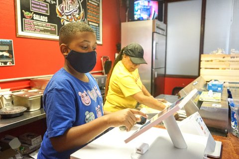 A Black boy in a black mask working a touchscreen register next to a woman in front of a menu