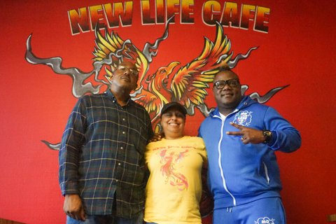 """Two Black men and a Black woman in front of a red wall painted with the words """"New Life Cafe"""" and a phoenix"""