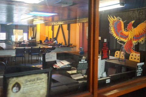 View through glass of three kids sitting a room full of tables and chairs, looking at a laptop. A phoenix is painted on one of the windows.