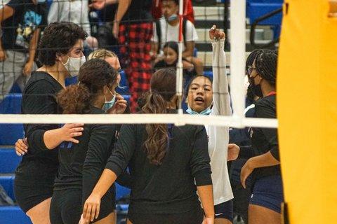 Girls' volleyball players seen through the net, huddled after a win.