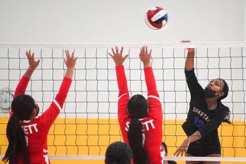 Volleyball game with player in black on one side and two in red on the other, all reaching for red, white and blue ball