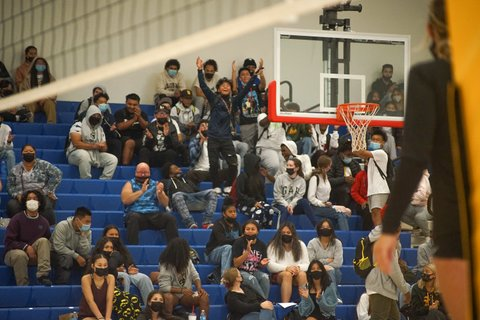 Fans at a game inside a high school gym