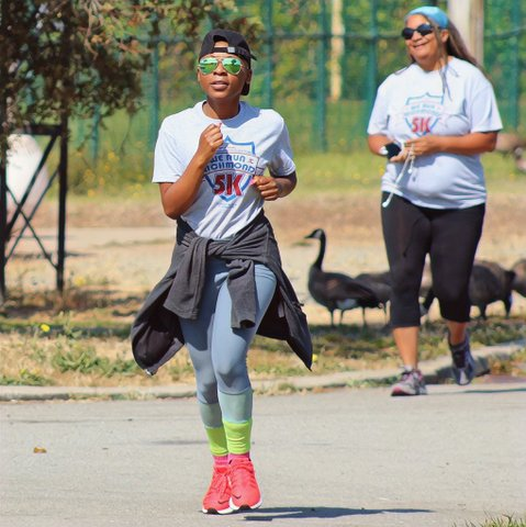 A Black person running in backwards baseball cap, green aviator sunglasses, We Run Richmond 5K T-shirt, jacket tied around their waist, blue pants, green socks and reddish shoes