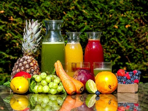 Fruits and vegetables on a table with three glass carafes of different juices
