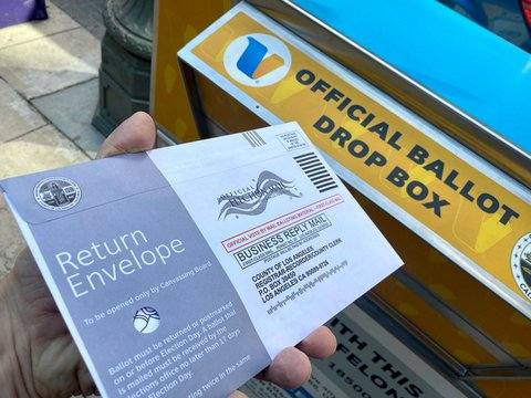"""Hand holding a sealed envelope marked """"official election mail"""" in front of an official ballot drop box"""