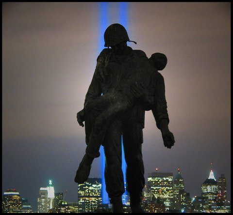 Silhouette of a soldier carrying someone with New York City and two vertical blue lights in the background
