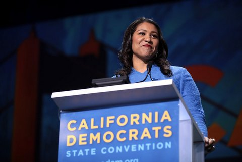 """A smiling Black woman in blue at a lectern that says """"California Democrats State Convention"""""""