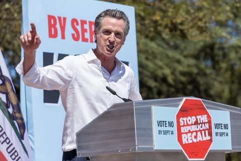 """Gavin Newsom at a lectern with a stop sign-shaped decal that says """"Stop the Republican recall"""""""