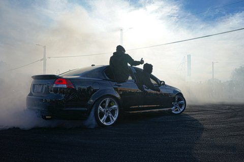 Black car in a smoky setting with one passenger sitting on a doorframe and another leaning out a window