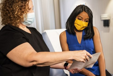 A white woman holds up a paper for a Black woman to read. Both are wearing medical masks.