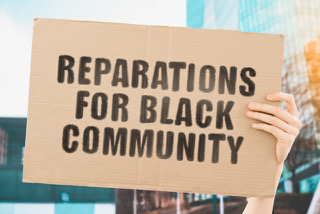 """Illustration of a white hand holding a sign that reads """"reparations for black community"""""""