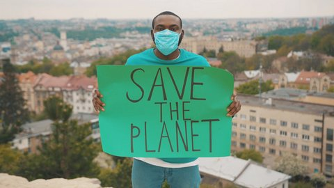 """A Black man in a respiratory mask holds a sign that says """"Save the planet"""""""