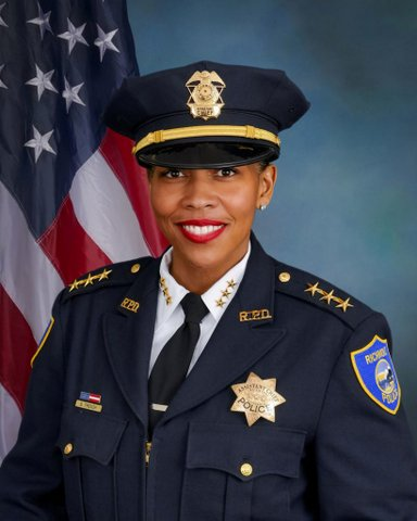 """A Black woman police officer in dress uniform with badge that says """"assistant chief"""" in front of the U.S. flag."""
