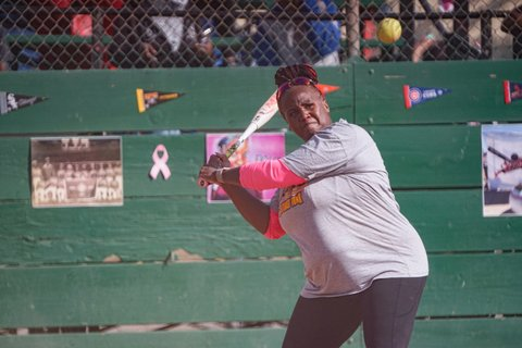 A Black woman at bat during a softball game. She is wearing a gray T-shirt over a top with pink long sleeves.