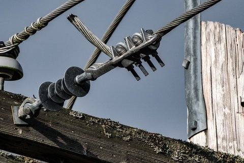 Close view of the insulators and power lines coming out of an electric pole