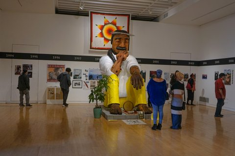A large sculpture of a Native American man in white shirt and yellow pants sits in a room surrounded by spectators and other artworks